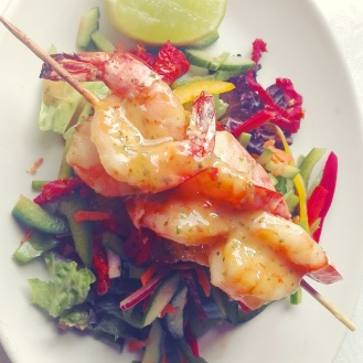 Garlic and lemon grilled prawn skewer on a green salad with a julienne of peppers, mange tout and cucumber drizzled with coriander and ginger dressing.