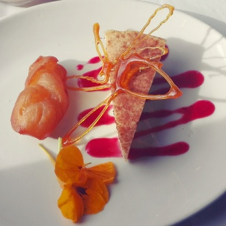 South African melktert served with fresh fruit coulis and a small syrup -coated doughnut (koeksister)